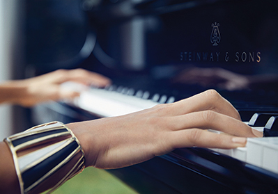 close up of woman's hands playing a Steinway piano