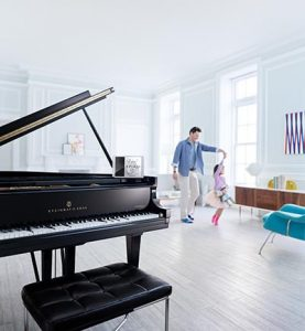 Dad and daughter dancing with Spirio grand piano