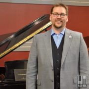 Mathew Powell in front of a piano.