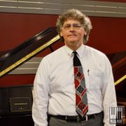Rick Fuchs in front of a piano.