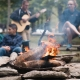Picture of a people playing the guitar around a campfire.